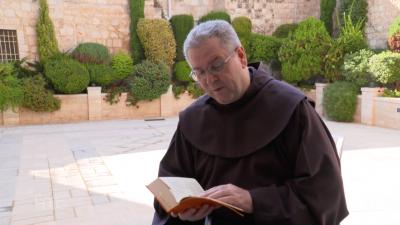 Fr. Francesco Patton prega all'aperto leggendo la Bibbia